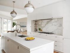 A pair of Hudson Valley Lighting Lambert Pendants hang over a white kitchen island with inset cabinets topped with thick white quartz fitted with a stainless sink and pull out faucet.