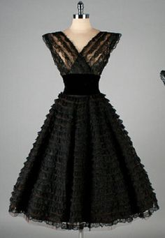1950's black lacey cocktail party dress. Full ruffled skirt, wide black velvet waist, fitted illusion bodice, v-neckline front and back. No maker label.