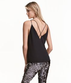 Black. Top in crêped woven fabric with a low-cut V-neck at front and back and narrow shoulder straps crossed at back. Lined.