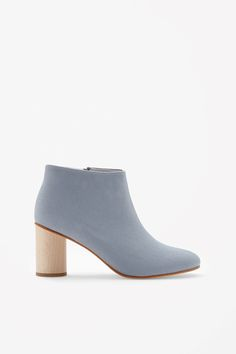 Made from cotton canvas with minimal detailing, these ankle boots have a round heel in light-coloured wood. Fastening at the side with a metal zip, they have a leather sole and lightly padded interior
