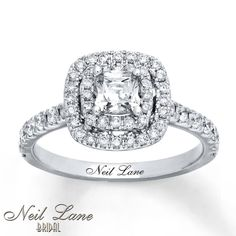 Rows of round diamonds surround a cushion-cut center diamond to create the dazzling main attraction of this engagement ring from the Neil Lane Bridal® collection. Additional diamonds embellish the gleaming 14K white gold band, for a total diamond weight of 1 1/8 carats. Diamond Total Carat Weight may range from 1.115 - 1.14 carats.