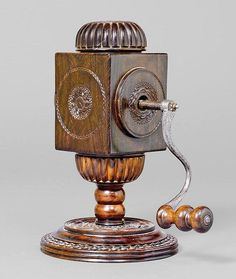 A LARGE SPICE MILL, possibly England or Holland, 18th c. Exotic wood turned and carved with flowers and frieze. Rectangular body on turned shaft and circular base. Hopper with screw top, iron crank with wooden handle. Grinder can be unscrewed to reveal grinds container.