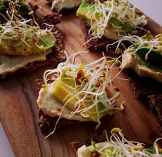 Pura Vida sprouted raw broccoli bread canapes with raw hummus, sliced avocado and sprouts, sprinkled with salt and ground black pepper!