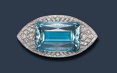 AN ATTRACTIVE ART DECO AQUAMARINE AND DIAMOND BROOCH, BY GILLOT & CO.   Centering upon a rectangular-cut aquamarine, weighing approximately 83.97 carats, within an old European, circular and single-cut diamond navette-shaped pierced surround, mounted in platinum, circa 1920  Signed Gillot & Co.