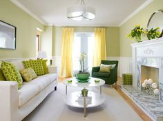 Lovely spring green & yellow contemporary living room design with butter yellow silk drapes, French doors, ivory sofa, green throw pillows, round modern coffee table, fireplace with white carrara marble, green accent chair, round mirror and white modern pendant. ivory green yellow living room colors.  I like the simplicity. It's uncluttered.