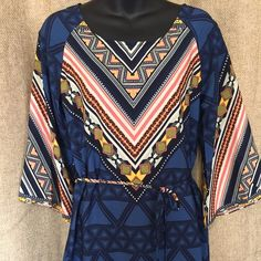 Aztec dress with tie at waist Navy dress by Pink Owl. Dress has a mixture of bright colors and Aztec type pattern. Round neck and belted at the waist. It is fully lined. Material is 100% polyester. The neck has a pulled thread at top shown in 3rd picture. Never worn NWOT. Pink Owl Dresses Mini