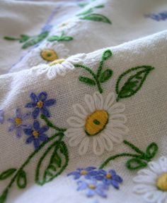 embroidered daisies.  love the white on white with purple accents.