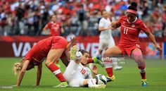 Ramona Bachmann of Switzerland challenges for the ball with Lauren Sesselmann and Desiree Scott of Canada during the FIFA Women's World Cup 2015 Round of 16 match between Canada and Switzerland at BC Place Stadium on June 21, 2015 in Vancouver, Canada.