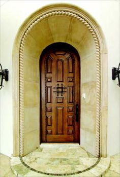 WELCOME HOME: The homes front entry, carved into the elbow of an intimate court, is flanked by stone fountains and wrought-iron lamps. Its splayed stone surround provides a dramatic frame for a 9-foot, hand-carved, knotty alder door.