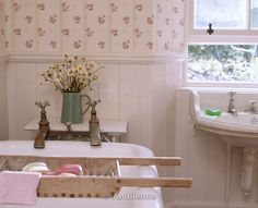 Ambience Images | Old wooden bath rack on white rolltop bath with reclaimed taps in cottage bathroom with panelling and floral wallpaper