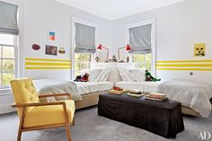 The walls of a children's room are painted in a Vicente Wolf white for PPG Pittsburgh Paints and accented with racing stripes in a Benjamin Moore yellow   archdigest.com