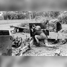 Dutch boys plays with a British anti-tank gun in Arnhem, 1945.