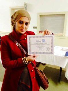 Basma Alawee holding up her certificate.