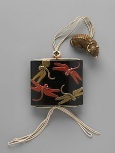 Case (Inrō) with Design of Dragonflies. Kōami Nagataka (dates unknown) (Japanese) Period: Edo period (1615–1868) Date: mid-18th century Culture: Japan Medium: Case: gold and red lacquer on black lacquer with mother-of-pearl inlay; Fastener (ojime): ivory carved with design of persimmon; Toggle (netsuke): ivory carved in the shape of a dog. The Metropolitan Museum of Art.