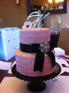 Princess baby shower cake with diamonds - This was for a princess themed baby shower.  The mother to be wanted to incorporate diamonds in the cake.  The bow is black ribbon with diamond brooch attached.  Cake was just covered in silver draggees all over.  The anemone flower on top is made out of gumpaste.