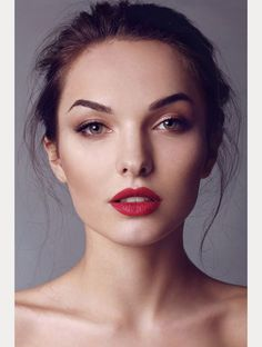 Bronzed/golden, dewy skin, understated eye with lots of white/golden highlight, sculpted brow, statement lip