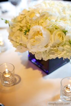 White flowers with colored short square vase as an alternative to the mixed height vases, or on some tables with others having taller mixed vases to make it vary throughout the room