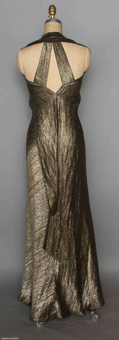 "GOLD LAME EVENING GOWN, 1930s (back view) Small abstract patterned lame, bias-cut, V neck w/ halter, low-cut back w/ 2 straps, 2 floating back panels, B 35"", W 26"", H 37"", L 57"""
