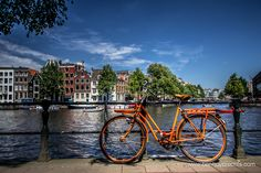 City of Amsterdam - by Ben Huybrechts Photography  In this image I tried to capture all things which come to mind when thinking of Amsterdam: bicycles, canals, bridges, houses, .... The orange color of the bicycle was a nice extra.