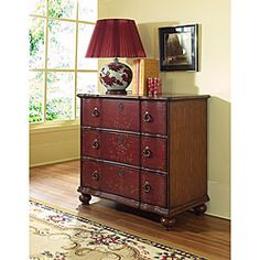 Large chest features a hand-painted leaf and scroll motif  Furniture is made of hardwood and MDF  Chest has a brown finish with ruby red drawers