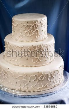 Elegant ivory wedding cake with a piped embroidered lace design by Karen H. Ilagan, via ShutterStock
