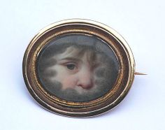 A gold, ivory and crystal eye miniature brooch portraying a child's eye amid dark clouds, symbols of mourning. (rowanandrowan.com)