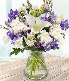 An incredibly beautiful bouquet of white Lilies, Spray Chrysanthemums and Carnations mixed with blue Irises and lilac Lisianthus for that classy look.