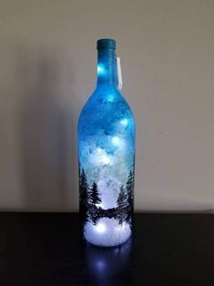 One foot string of fairy lights included! Bottle is 14 inches tall, inches wide. Painted Glass Bottles, Blue Glass Bottles, Glass Bottle Crafts, Wine Bottle Art, Lighted Wine Bottles, Bottle Lights, Decorative Glass Bottles, Crafts With Wine Bottles, Decorated Wine Bottles