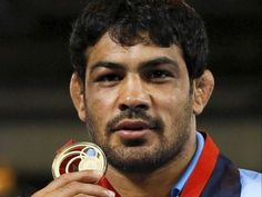Indian wrestler Sushil Kumar poses with his gold medal at the Commonwealth Games 2014.