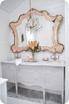 double sink in an old antique buffet with a rose gold vintage mirror and chandelier. pretty romantic.