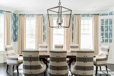 These broad striped seats have a button detail to the rear to add interest. The space feels serene thanks to the simple off-white floor-length curtains framing the timber sash windows. A Chinese patterned blue and white wallpaper adds another layer of personality and contrasts strongly with the simple classic shape of the dining table.