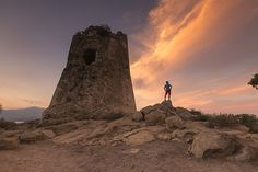 Hiker admires sunset from the stone tower overlooking the bay Porto Giunco Villasimius Cagliari Sardinia Italy Europe