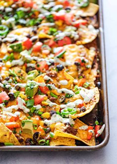 Loaded Sheet Pan Nachos! Whether we're talking a casual movie night with the family or Super Bowl Sunday, these Loaded Sheet Pan Nachos are ready to party! They come together quickly and easily, and are so much fun to each straight from the pan. #simplyrecipes #nachos #sheetpan #superbowl #gameday #football