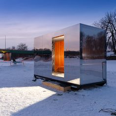 A mirrored hideaway and a pop-up art gallery are among the shelters littered along the banks of a frozen river in Winnipeg for the Warming Huts competition.