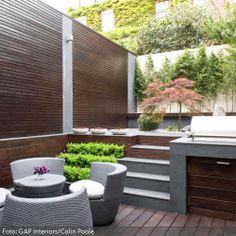 Dunkles, bearbeitetes Holz dient auf dieser Terrasse als Bodenbelag und Sichtschutz. Treppen aus Steinfliesen führen zu einem integrierten Podest, auf dem kleine Pflanzen, ein roter Ahorn und andere Bäumchen aus hellem Kies hervorsprießen. Die üppigen Stühle aus grauem Rattan haben eine rundliche Form und wirken mit ihren hellen Sitzpolstern sehr einladend. Die Outdoorküche ist das Highlight jeder Terrassen-Party.