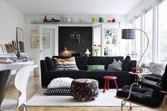 gemütliches Wohnzimmer in Weiß mit schwarzem Sofa in der Mitte