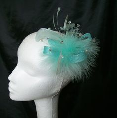 Aqua Ophelia Fascinator Comb Order Now from www.indigodaisyweddings.co.uk Specialising in stunning bespoke cocktail fascinators and formal hats in a wide range of colours, perfect for Royal Ascot and The Kentucky Derby. Plus all your wedding floral accessories including shoe clips, bandeau veils,vintage flapper bands, feather and flower fascinators, feather fans, fairy wands, wrist corsages, wedding bouquets & buttonholes. Worldwide Delivery.