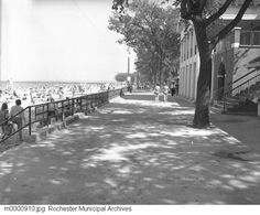 1953  A view of the boardwalk at Ontario Beach Park in Charlotte, also showing the beach and the bath house. The view is to the east.