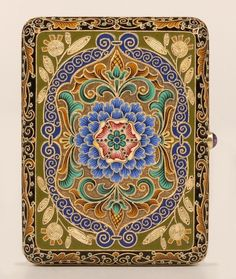 A Russian gilded silver and shaded and cloisonné enamel cigarette case, probably Feodor Rückert, Moscow, circa 1899-1908. Rounded rectangular, enameled with a stylized sky blue and red chrysanthemum within stylized green fronds against a stippled gilt ground, reserved within borders of green enamel applied with stylized flowers formed of twisted cables, the outer borders of black enamel against which are enameled stylized flowers of mustard yellow and teal beads, with cabochon amethyst…