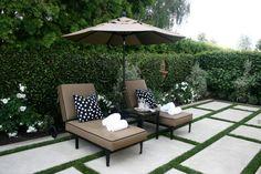 aménager son jardin avec dalles et gazon, chaises longues et parasol marron