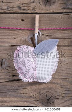 Decorative cushions shaped apple hanging on clothesline on old wooden background