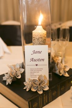 Book theme centrepiece - each table is named after an author, flowers made out of book pages and candle created using oil based paint on a stamp