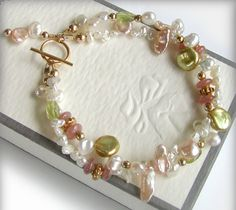 Multi strand Keishi Pearl bracelet with Peridot, Rohodochrosite and 14k Gold Filled accents. This designs features a huge variety of Keishi pearls in ivory, pink, peach and green ... these beauties are super lustrous with amazing overtones. Petite high quality faceted Peridot and smooth Rhodochrosite rondelles perfectly accent the pearls, while the generous use of 14k gold filled adds to the richness of this feminine design. Bracelet measures 7 1/8 including clasp My Etsy shop: htt...