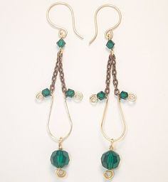 These slender, elegant earrings catch the light beautifully as they swing, and are vintage-inspired with subtle modern touches. Emerald Green Swarovski crystals with a small red brass spiral dangle fr