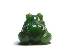 A nephrite frog by Carl Fabergé,     carved from a single piece of nephrite in a crouched position,  its eyes set with rose diamonds, the rounded form and  observation of the animal's musculature displays the  influence of Japanese works of art on Faberge's  hardstone carvings.