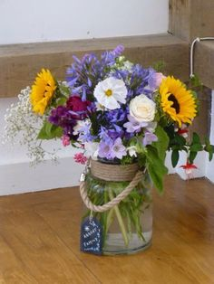 The Mother-of-the-Groom created a special jar of flowers for the wedding with the favourite flowers of the grandparents that had died. We then titled it with a slate label 'absent family'.  There were sunflowers, stocks, roses etc.
