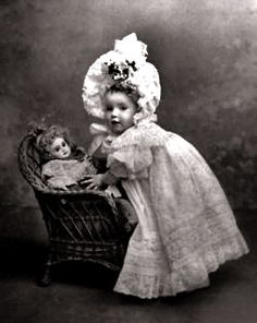 French antique portrait of a baby girl posing with her Bébé Jumeau doll, c. 1890-1900