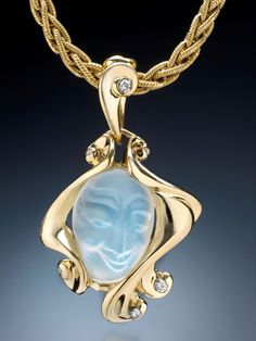 Carved moonstone face in a sculpted 18k yellow gold pendant with diamonds
