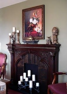 Faux fireplace.  Long shelf (mantel), tile around black center (paint, felt, foam bd.),   elevated board or box on floor (hearth), tall candles (fire), real fireplace screen.