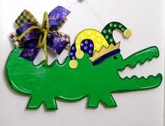 Celebrate the season with this Mardi Gras Alligator Door Hanger. Made of wood and hand painted. The back is painted white for a finished look. This whimsical Alligator Door Hanger measures 28 by 14 tall not including the bow. This door hanger has been sealed and is safe for outdoor use. A wire is attached for quick and easy display. Ribbons may vary but will always coordinate with the design.  I recommend hanging this door hanger under a covered porch or patio to protect it from the direct…